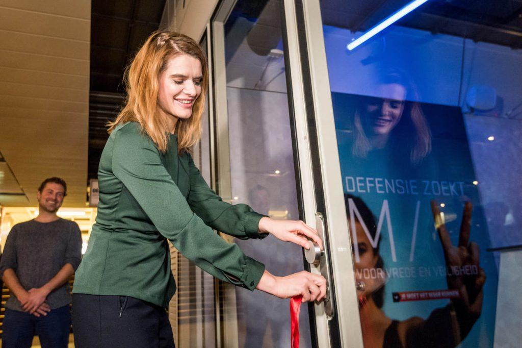 """Amsterdam, 16 november 2017 Staatssecretaris van Defensie (Stas) Barbara Visser opende donderdag 16 november om 11.00 uur in Amsterdam de eerste Defensie """"pop up store"""". Deze winkel is gevestigd in de Amstelpassage van het Centraal Station van Amsterdam en zal een maand open zijn. De winkel laat het publiek kennis maken met Defensie als veelzijdige werkgever. De """"pop up store"""" heeft o.a. een escaperoom waarin je te maken krijgt met militaire vaardigheden zoals samenwerken en omgaan met tijdsdruk. Ook zijn er recruiters aanwezig die ter plekke alle vragen van geïnteresseerden in een baan bij de krijgsmacht beantwoorden."""